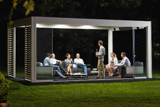 une soirée entre amis sous une pergola bioclimatique à lames orientables, panneaux coulissants verre et panneaux loggia, lames leds et système de chauffage intégré