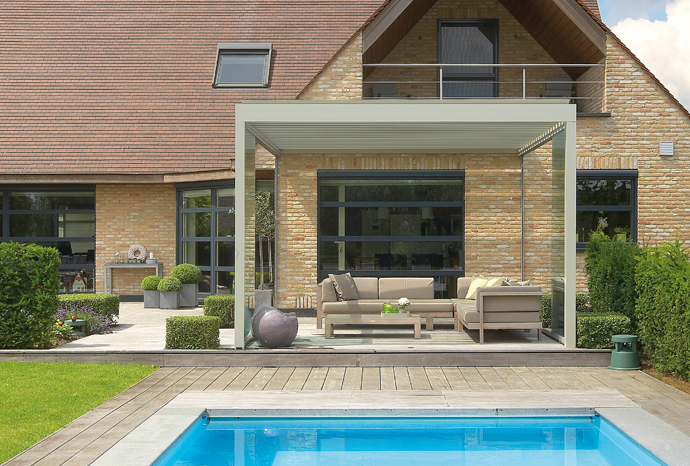 une pergola bioclimatique couvre un magnifique salon de jardin à proximité d'une piscine