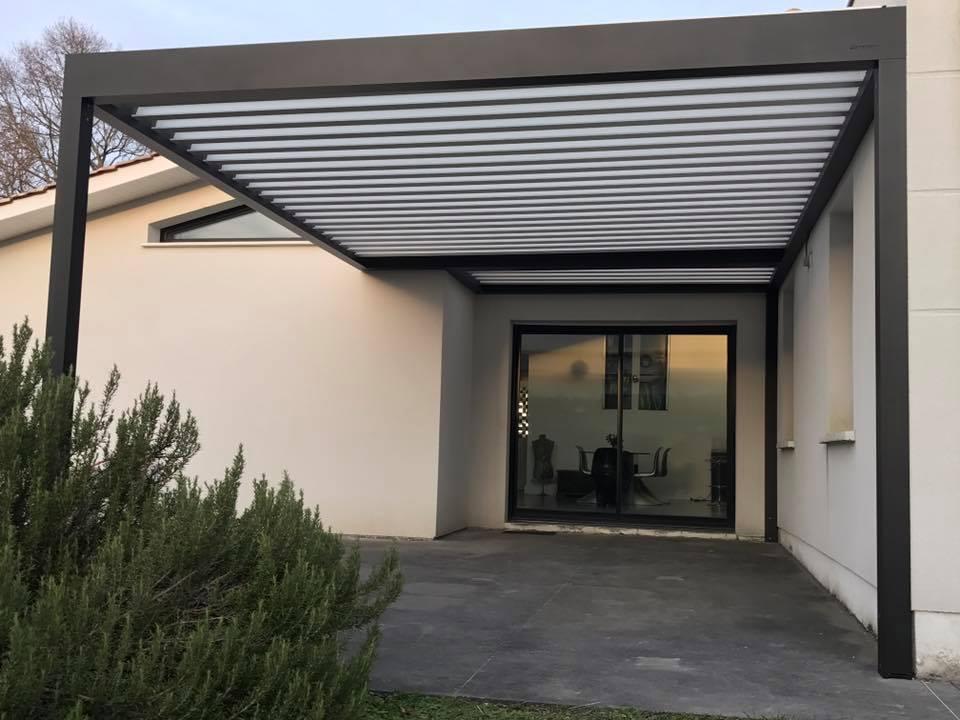 une pergola bioclimatique sur mesure devant une baie vitrée et deux fenêtres dans l'angle d'une maison en gironde