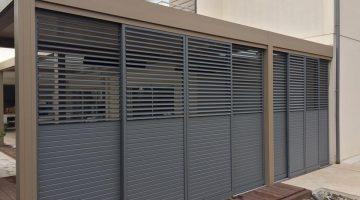 8 panneaux coulissants loggia gris installés sur un côté d'une pergola bioclimatique sur mesure