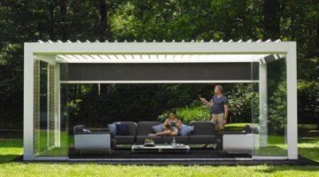 un couple installé sous une pergola bioclimatique dont les lames sont ouvertes. L'homme est en train de fermer un store à l'aide de sa télécommande