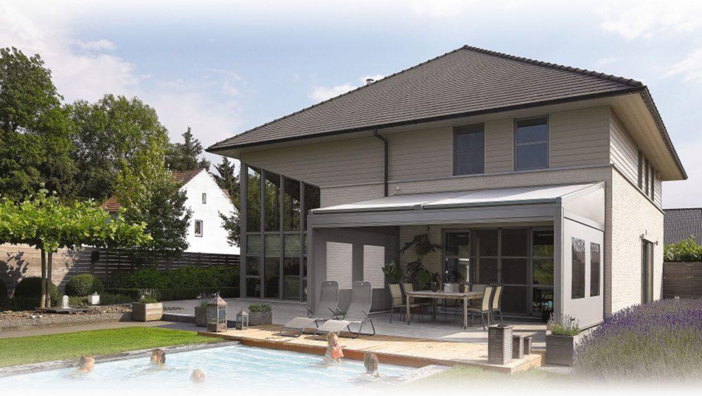 une terrasse couverte avec une pergola inclinée. Il s'agit d'une pergola store modèle Lagune de Renson