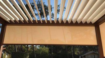 les lames orientables de cette pergola laissent passer l'air tandis que les stores protègent du soleil