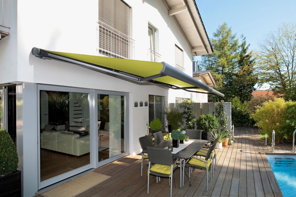 un store markilux 5010 de couleur verte sur la terrasse bois d'une maison