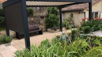 une pergola bioclimatique à lames orientables et stores de côté installé sur le patio d'une maison ancienne chez un particulier en gironde