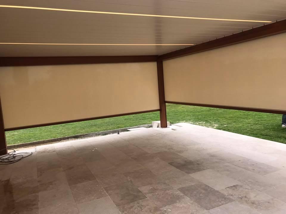 une pergola bioclimatique à lames orientable complètement fermée avec des stores automatiques sur les côtés