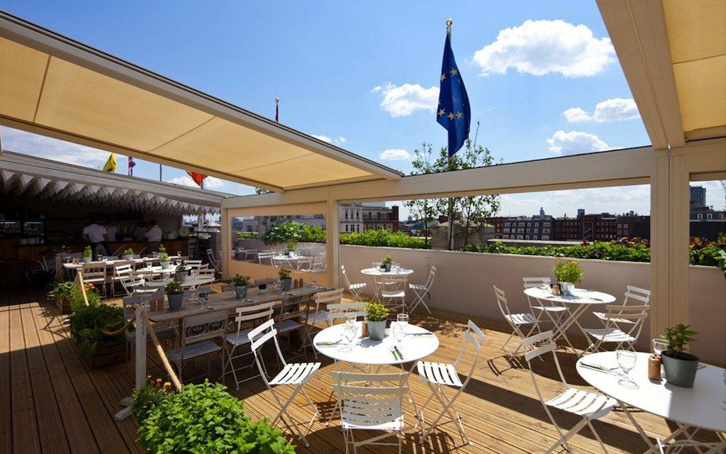 Une couverture terrasse restaurant réalisée avec une pergola store Lagune de Renson