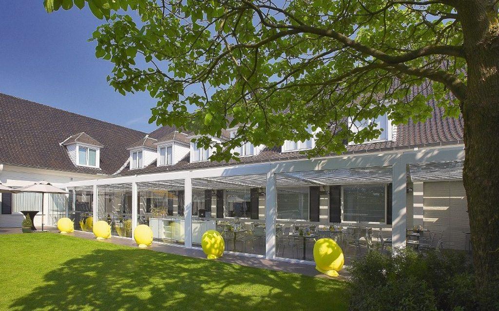 terrasse d'un restaurant entièrement couverte et fermée par une pergola bioclimatique camarge et des panneaux coulissants verre