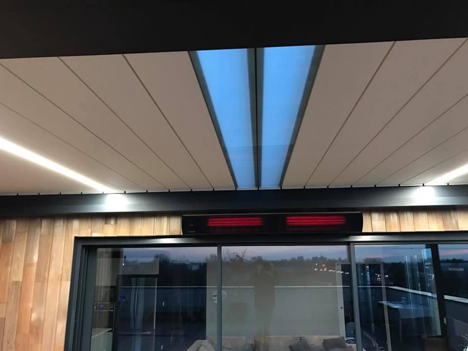 vue du chauffage, des lames transparentes et des lames led d'une pergola bioclimatique à lames orientables