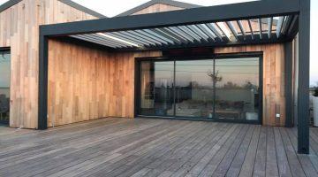 une pergola bioclimatique à lames orientables et chauffage intégré sur la terrasse d'un hôtel